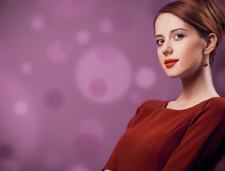 Beautiful redhead woman in red dress on viloet background.
