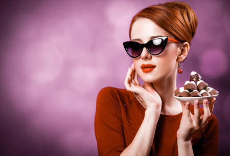 Redhead woman with candy on violet background. Stock Photo