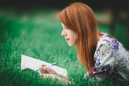 Young beautiful redhead girl with notebook on green lawn in a park. Spring time season Stock Photo
