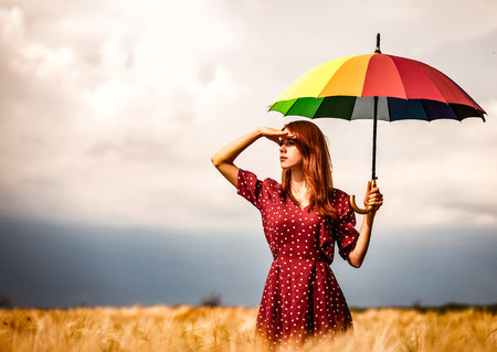 a young girl is standing on a wheat field with umbrella and waiting for rain.