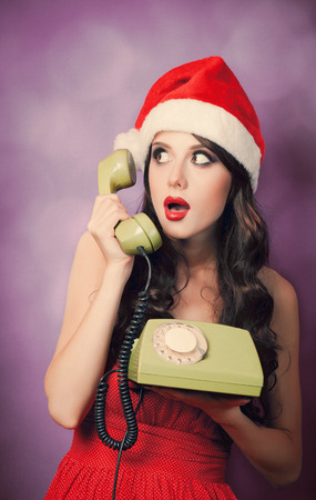 Beautiful brunet girl in christmas hat with green telephone on violet background.