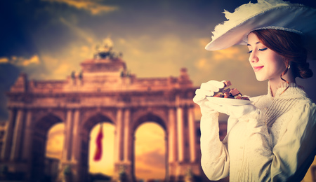Redhead woman with belgian candy on arch background Stock Photo