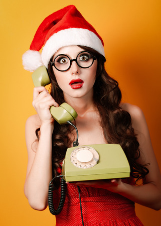 Beautiful brunet girl in christmas hat with telephone on yellow background.