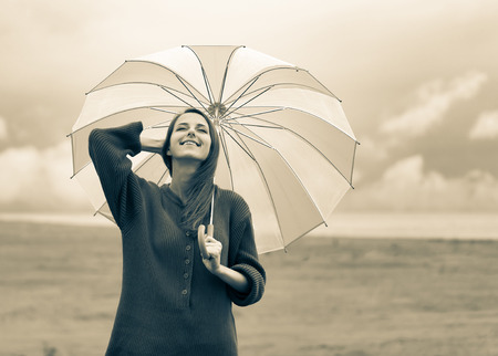 Beautiful adult girl in sweater with umbrella at wheat field and cloudscape on background. Image in sepia color style