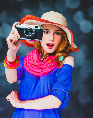 Stylish redhead girl in hat with camera and bokeh on background