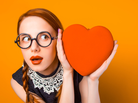 surprised young girl in glasses with two pigtails holding heart shape box on yellow background