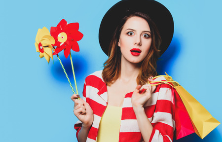 Portrait of young surprised red-haired white european woman in hat and red striped shirt with pinwheels and shopping bags on blue background