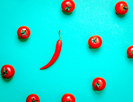 Above view at chili pepper and tomatoes on green background Stock Photo
