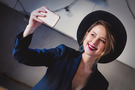 Young girl in black hat and dress and make a selfie on mobile phone.