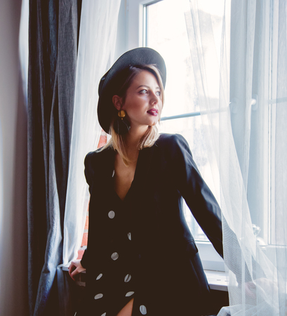 Young redhead girl in black hat and jacket with polka dot dress stay near window.