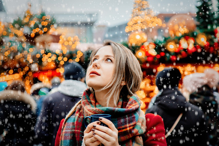 Beautiful adult girl with cup of hot drink at Christmas fair in Dresden, Germany