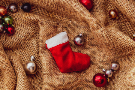 Christmas sock and baubles in Santa Claus hat on jute background