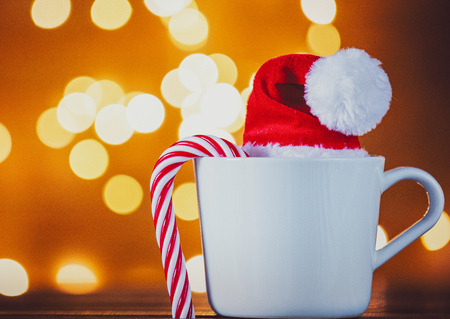 White cup of tea or coffee with candy cone and Christmas Lights on background Stock Photo