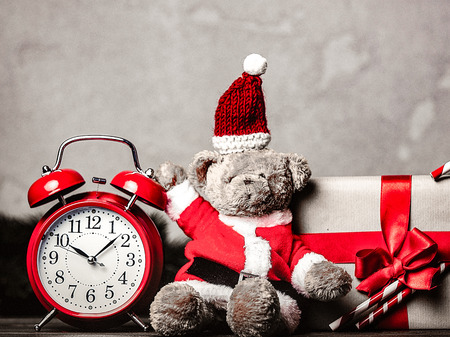Christmas gift with bowknot and retro alarm clock near teddy bear toy on grey background Stock Photo