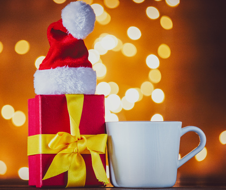 White cup of tea or coffee with gift box and Christmas Lights on background