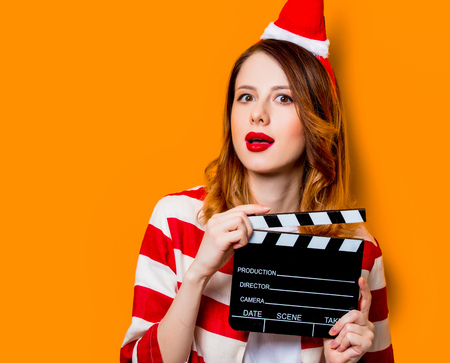 Portrait of young redhead woman in Santa Claus hat and striped shirt with filmmaking clapperboard on yellow background. Christmas time Stock Photo