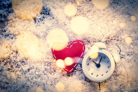Heart shape toy and Fairy Lights with alarm clock on snow background. Concept for Christmas or Valentines Day Holidays