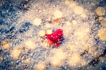 Heart shape toy and Fairy Lights on snow background. Concept for Christmas or Valentines Day Holidays