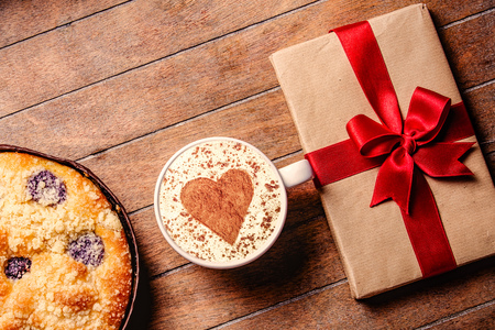 Christmas pie and cup of coffee with heart shape with gift boxes around on wooden table. Hight angle point of view