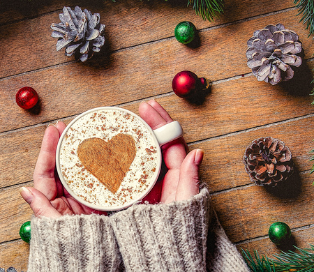 Womans hands holding Christmas cup of coffee with heart shape and candy on wooden table. Hight angle point of view Imagens