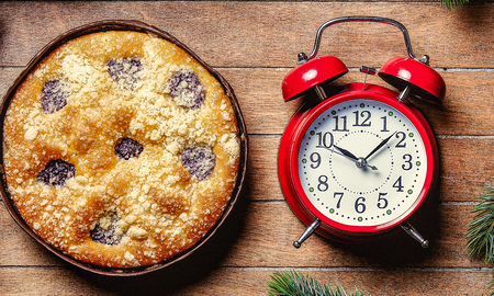 Christmas pie and little alarm clock on wooden table. Hight angle point of view Imagens