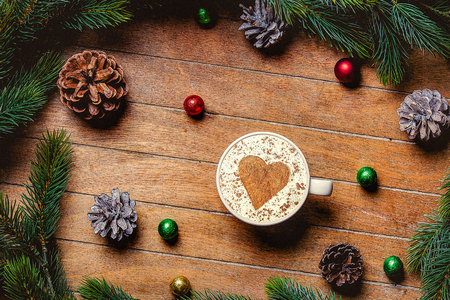 Christmas cup of coffee with heart shape and candy on wooden table. Hight angle point of view