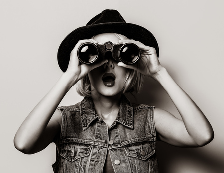 Portrait of young style hipster girl with binoculars on yellow background . Image in black and white color style.