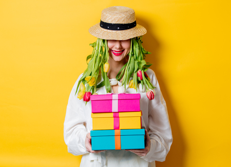 Beautiful woman in white shirt and hat with fresh springtime tulips instead hair and gift box on yellow background