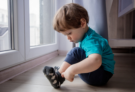 little toddler boy sitting on floor near window and looking at foots