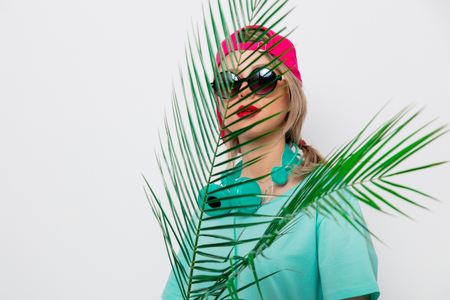 Beautiful young girl in pink cap and blue t-shirt with green palm branch on white background. Stock Photo