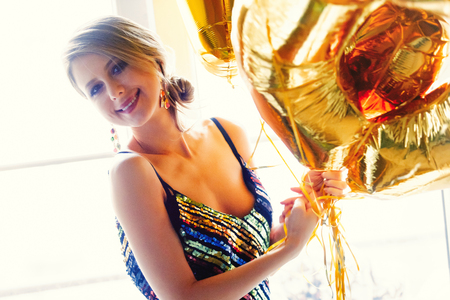 Young woman with golden balloons on her thirty years birthday. Indoor location. Person is in vintage 80th dress and hairstyle. At home