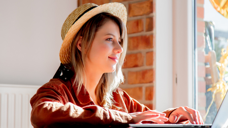 Young girl in hat looking in Internet via laptop for a summer vacation