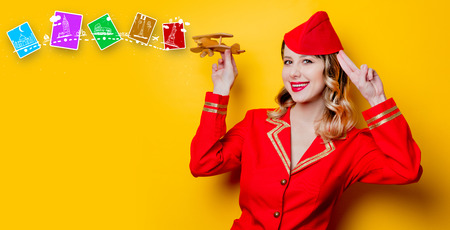 Portrait of charming vintage stewardess wearing in red uniform with wooden airplane. Isolated on gray background.