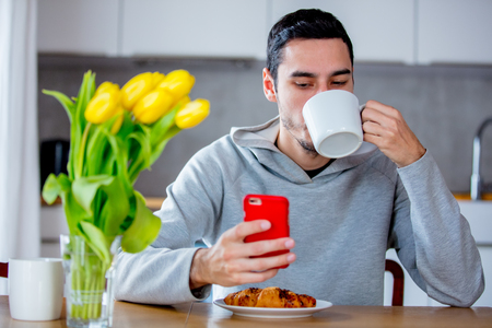 Young handsome man sitting at table with cup of coffee or tea and mobile phone. Kitchen location in morning Reklamní fotografie