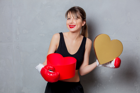 Young woman in boxing gloves with heart shape gift box in hands on gray background