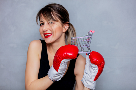 Young woman in boxing gloves with shopping cart on gray background. 90s flashlight style