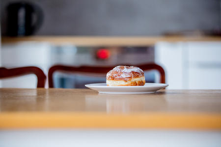 Donut on white plate on wooden table at kitchen in a morning