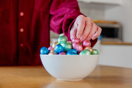female hands try to take Easter eggs in plate on a wooden table at kitchen in home