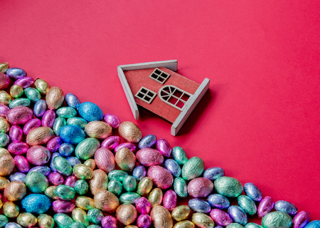 color Chocolate Easter eggs and toy house on red background