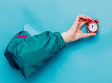 Female's hand in 90's style jacket holding alarm clock on blue background