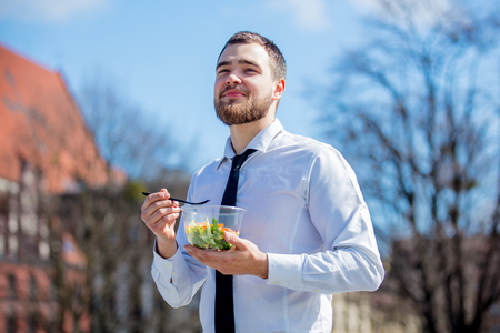 Young businessman in shirt and tie with salad lunch box on outdoor in sunny day.