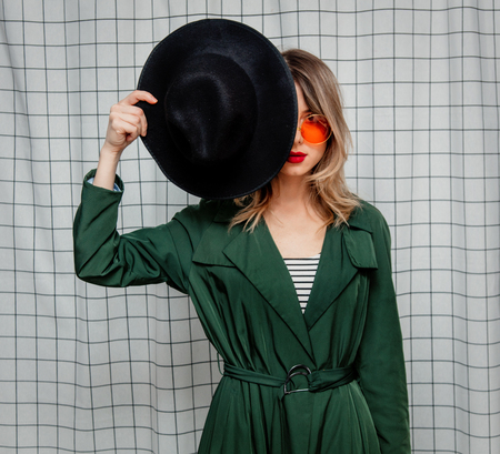 Young style woman in sunglasses and green cloak in 90s style stay on checkered background