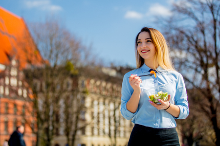 Young business woman with salad lunch box on outdoor in sunny day. Stock Photo