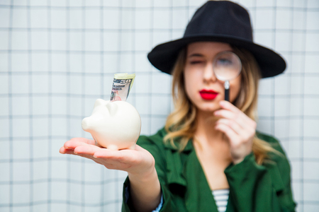 Young style woman in hat and green cloak in 90s style with magnifier and piggy bank stay on checkered background