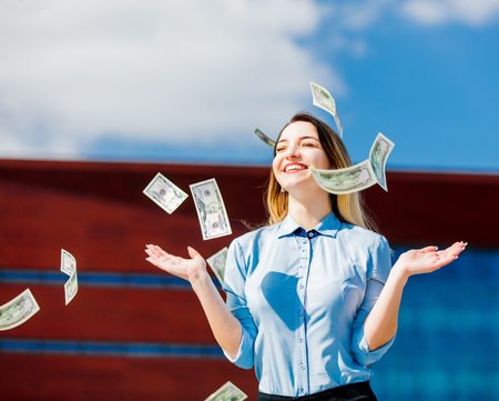 Young businesswoman with cash money at city outdoor.