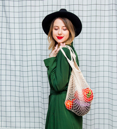 Young style woman in hat and green cloak in 90s style with net bag stay on checkered background