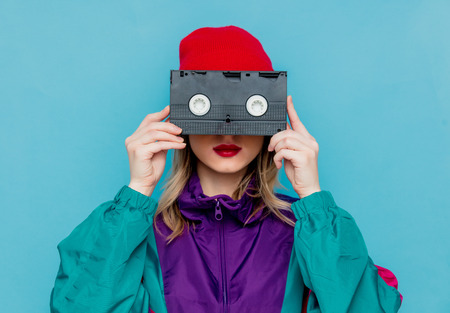 Portrait of a woman in red hat, sunglasses and suit of 90s with VHS cassette on blue background.