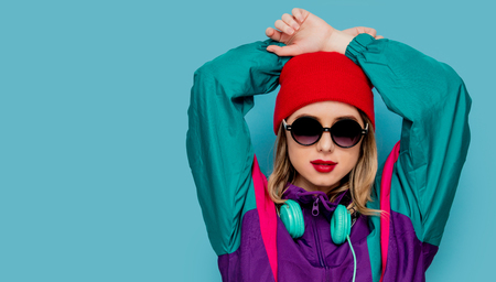 Portrait of a woman in red hat, sunglasses and suit of 90s with headphones on blue background.