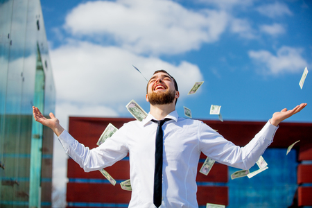 Young businessman with falling cash money at city outdoor.