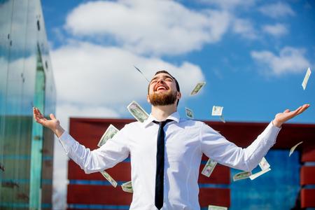 Młody biznesmen z spadające pieniądze w gotówce na zewnątrz miasta. Zdjęcie Seryjne